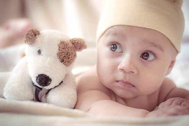 empathy - cute baby on bed with dog doll.