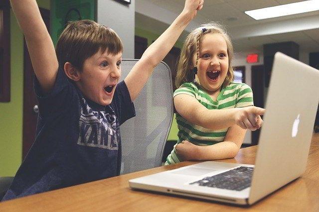 children using laptop computer enthusiastically