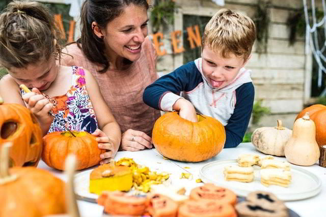 creativity - two children and their mother are curving pumpkins