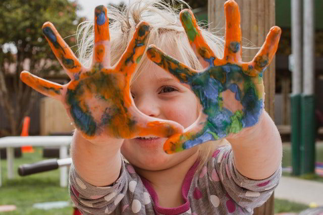 creativity - little girl showing painted hands