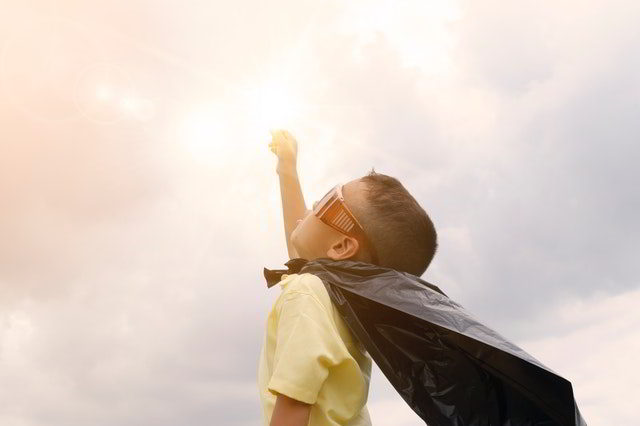 little boy with cape and sun glasses aims for the sky