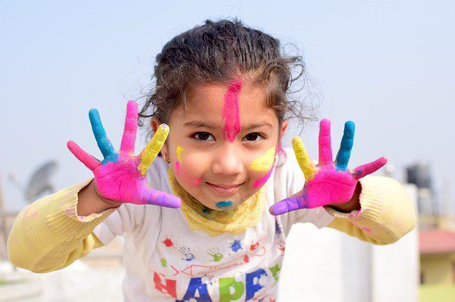 Little girl showing her hands and face covered in paints