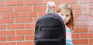 Absenteeism - young girl showing school bag.