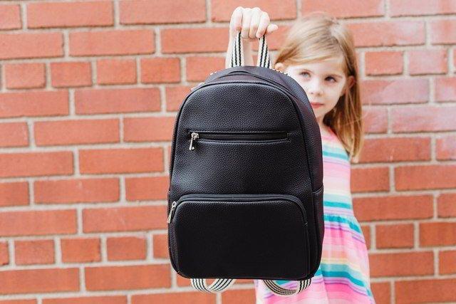Absenteeism - young girl showing school bag.