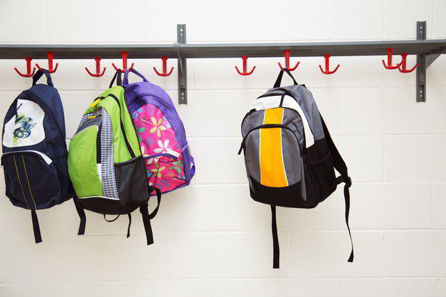 School bags hanging on rack.