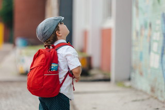 Absenteeism - young boy with school backpack.