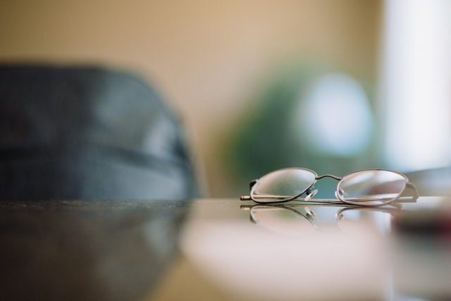Pair of reading glasses on table.