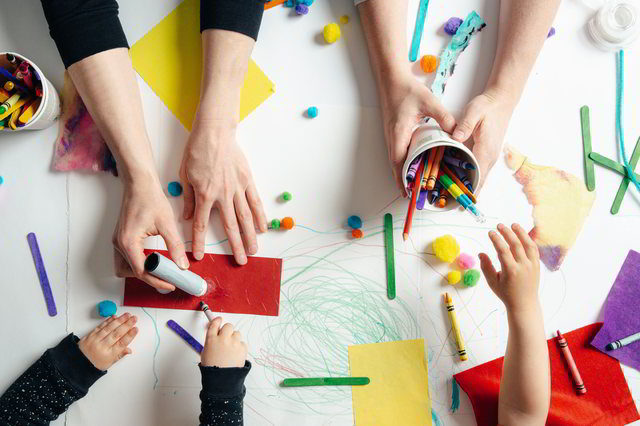 Educational psychologists helping young students with crafts.
