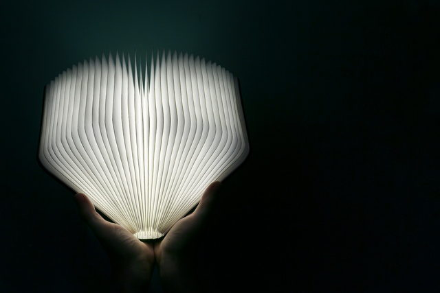 Pair of hands holding open glowing book in the dark.