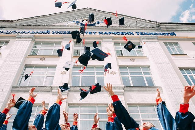 College graduates throwing hats in the air.