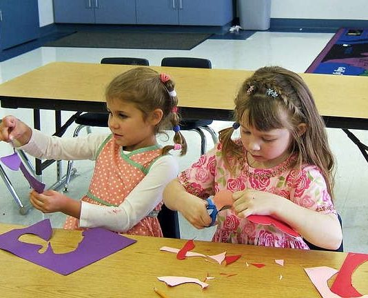 Choice time: two young girls doing arts and crafts