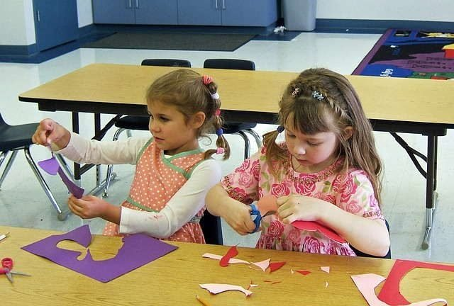 Two young girls doing a craft project on choice time.