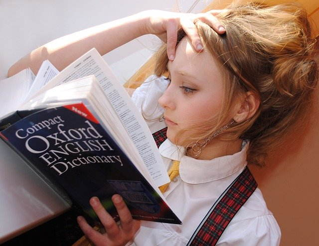 young girl studying english words from dictionary