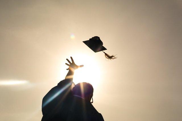 choosing a college: graduate throws hat in the air
